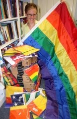 The Rev. Buchakjian-Tweedy displays some of the many Rainbow flags, banners and more that are now arriving daily from around the country and abroad, as a show of support for the LGBT community, in light of the recent thefts. (John Nolan/Times photo)